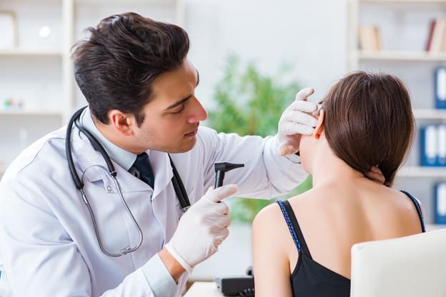 Лікар обстежує вушну раковину, щоб визначити ступінь запалення і підібрати вушні краплі від отиту